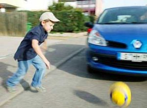 Child and ball on road